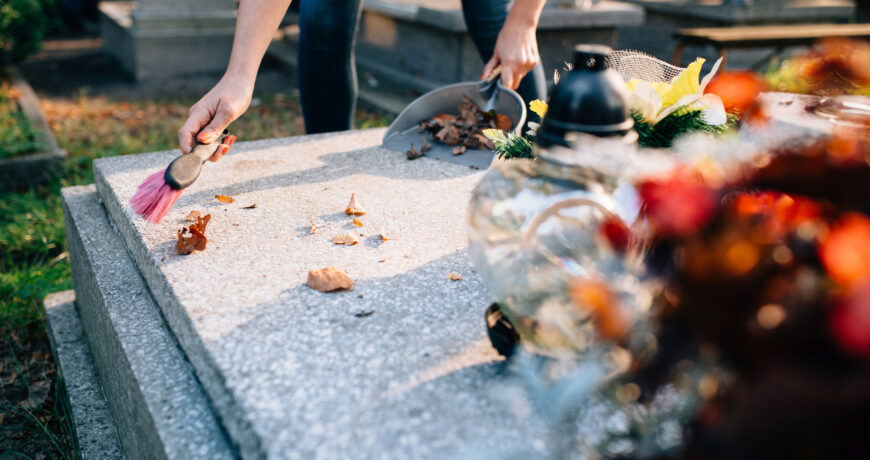 A woman cleans the grave. Sweeps leaves from the tombstone. Preparations for All Saints Day on November 1